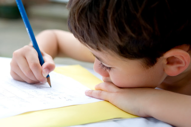 Menino escrevendo à mão com lápis no papel.
