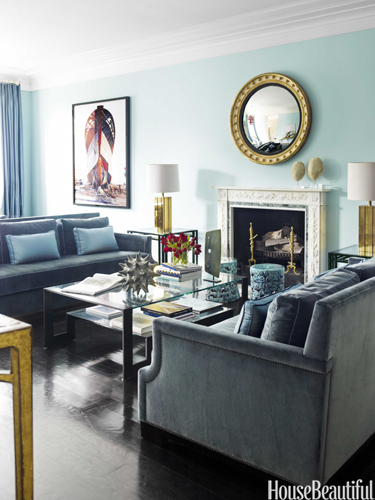 The circular mirror above the fireplace pairs well with the velvet couches.