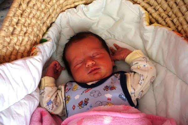 noworodek śpi z rączkami do góry w koszu mojżesza