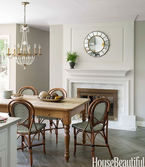 Paris bistro chairs at farm table in elegant traditional dining room with fireplace
