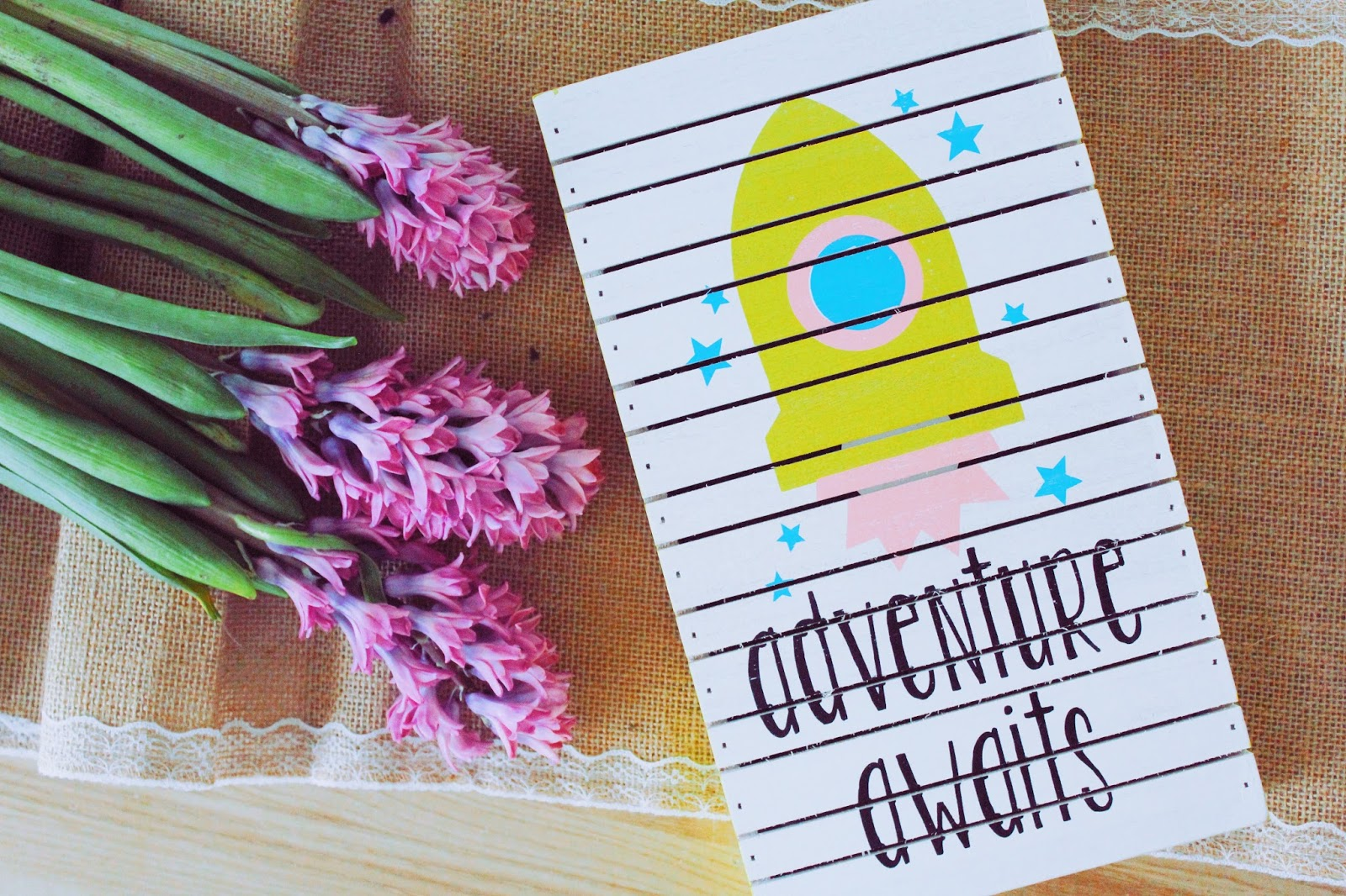Flowers and postcard saying adventure awaits