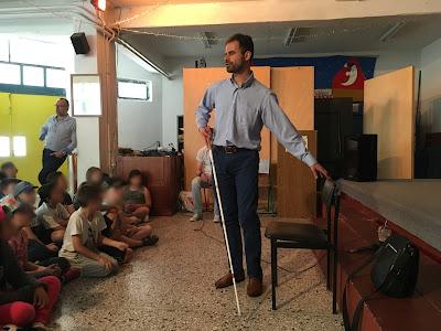 Ο Βαγγέλης Αυγουλάς δείχνει στα παιδιά πως βρίσκει την καρέκλα του για να κάτσει