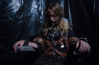Movie still for the horror movie Bad Samaritan where a woman, played by Kerry Condon, is help captive, tied up and chained to a chair in a dark room