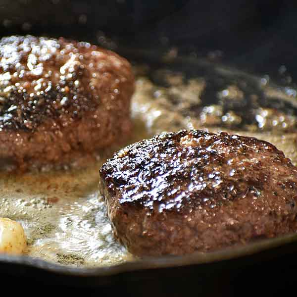 Burgers cooking in garlic butter on the stove in cast iron skillet