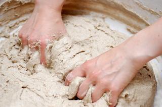 Hands mixing dough