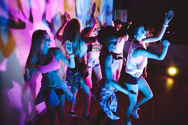 Image description: group of women dancing at a club or some such location