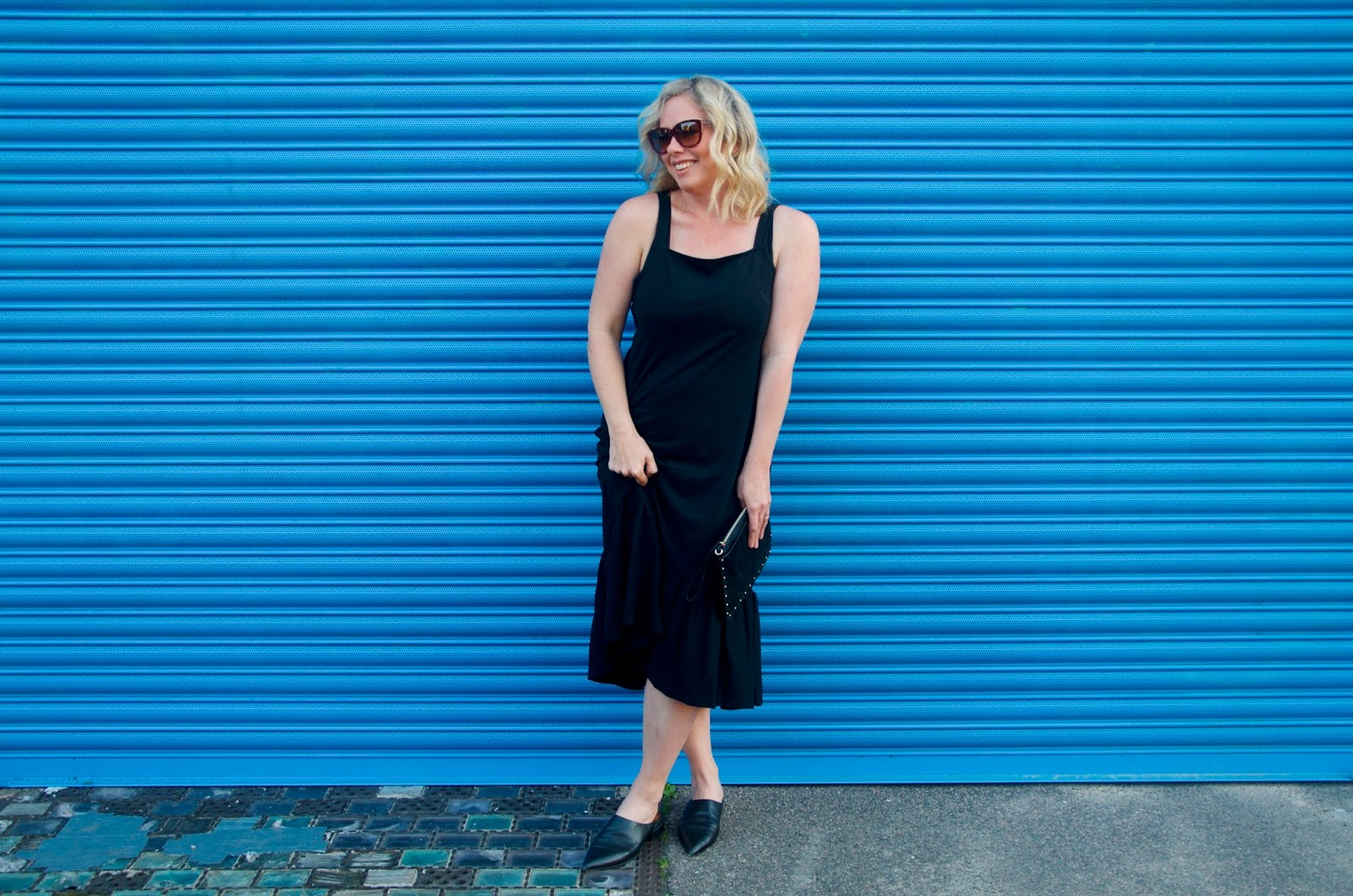 Black midi dress, black mules, black clutch, burgundy sunglasses and blue wall