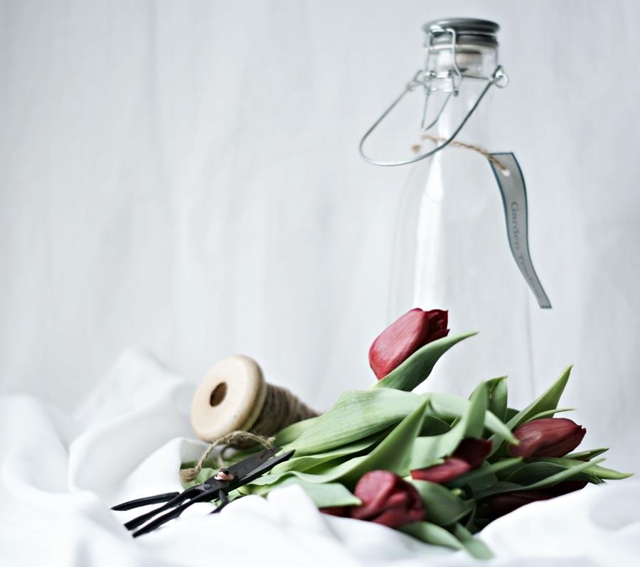 Blog + Fotografie by it's me! - Wohnen - rote Tulpen, eine Glasflasche und eine alte Schere