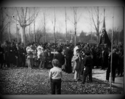 procesión de pueblo con gran muchedumbre alrededor de las imágenes. En blanco y negro.