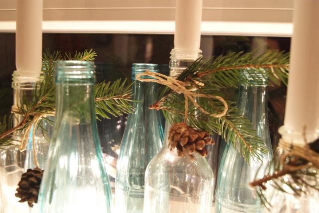 Flaschen mit Tannenzweigen und Zapfen weihnachtlich dekoriert