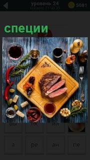 На разделочной доске лежит порезанное мясо на куски и вокруг находятся разные специи для приготовления мяса