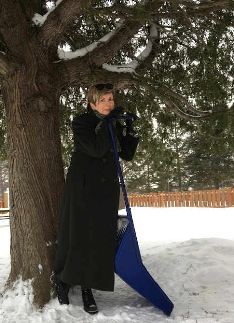 woman in a long coat leaning against a blue snow scoop