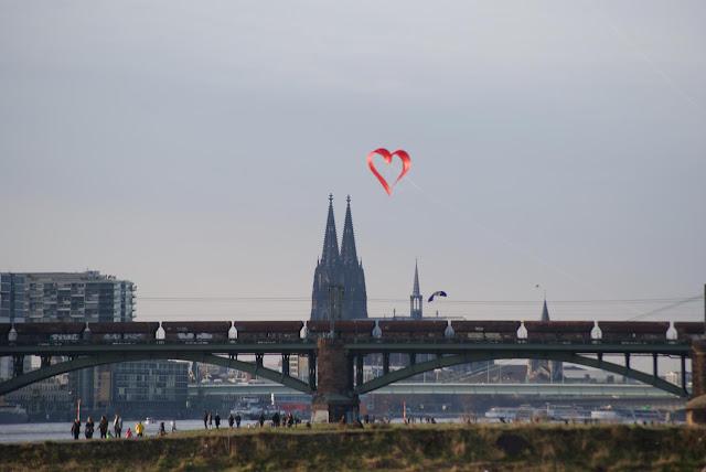 Ein Drachen in Herzform schwebt vor den Spitzen des Doms. Im Vordergrund fährt ein Güterzug über eine Brücke