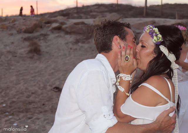 Beso de los novios, vestidos de blanco, con tocado TARIFA malonsilla