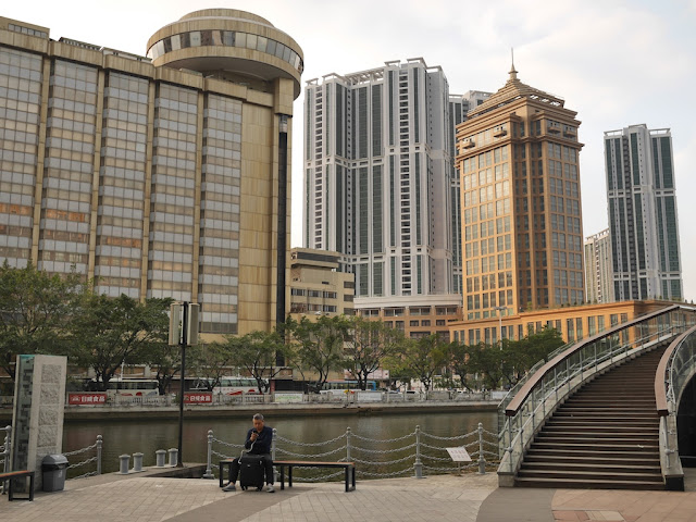 man using a mobile phone while sitting next to the Shiqi River with tall buildings in the background