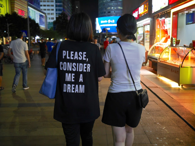 "two young women walking together; one is wearing a ""Please, consider me a dream"" shirt"