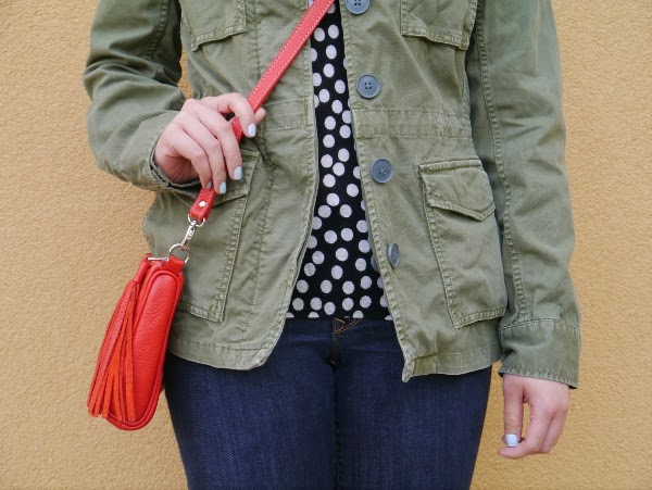 Army jacket, black-and-white polka dot sweater, pastel blue nails, red crossbody bag