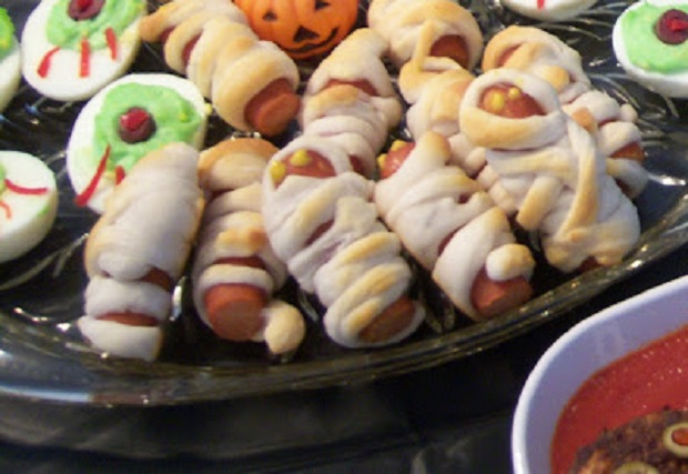 Creative and fun foods for a Halloween party Gravestone sandwiches, tangerine pumpkin fruit cups, apple peanut butter teeth, witches brew, mummy hotdogs, deviled egg eyeballs, donut eyeballs, dirt pies with worms, meatballs swimming in sauce faces, and English muffin faces