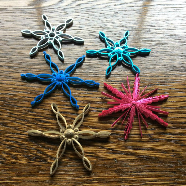 five modern quilled snowflake ornaments on table
