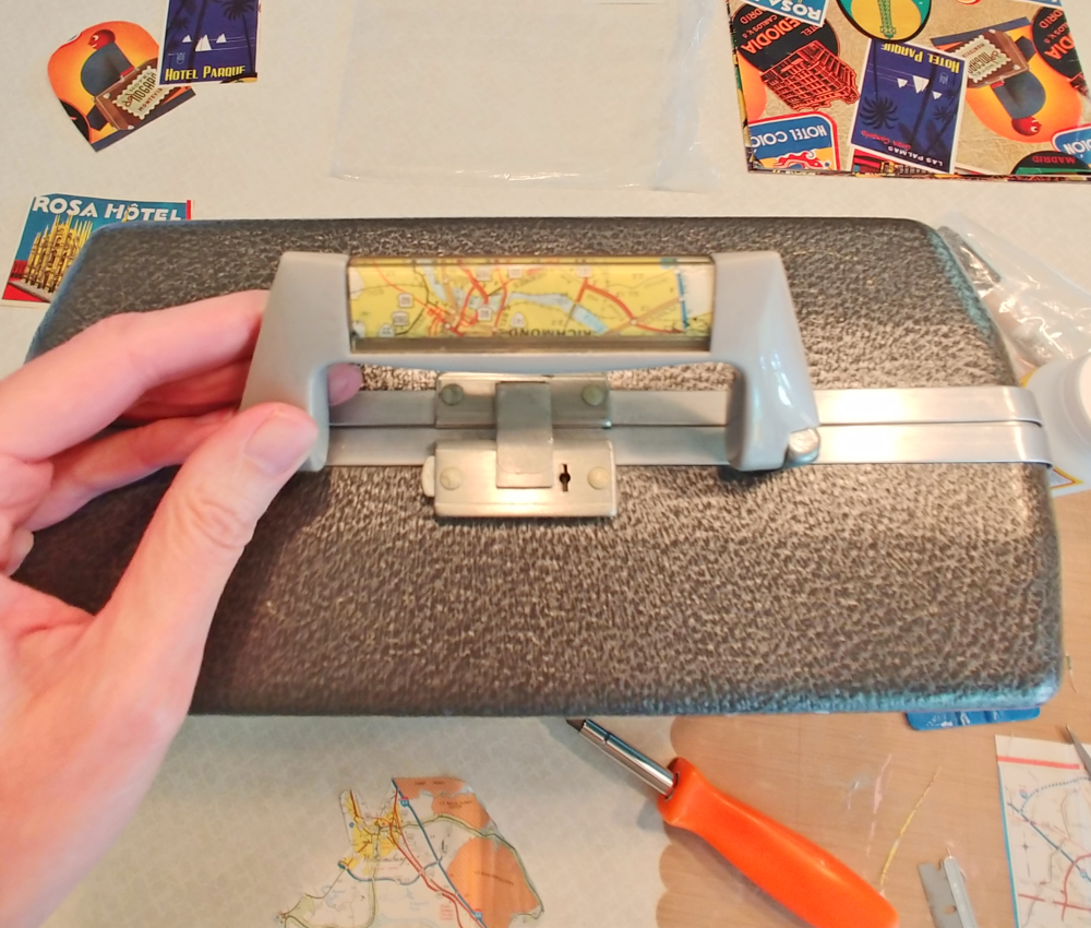 suitcase handle with map paper