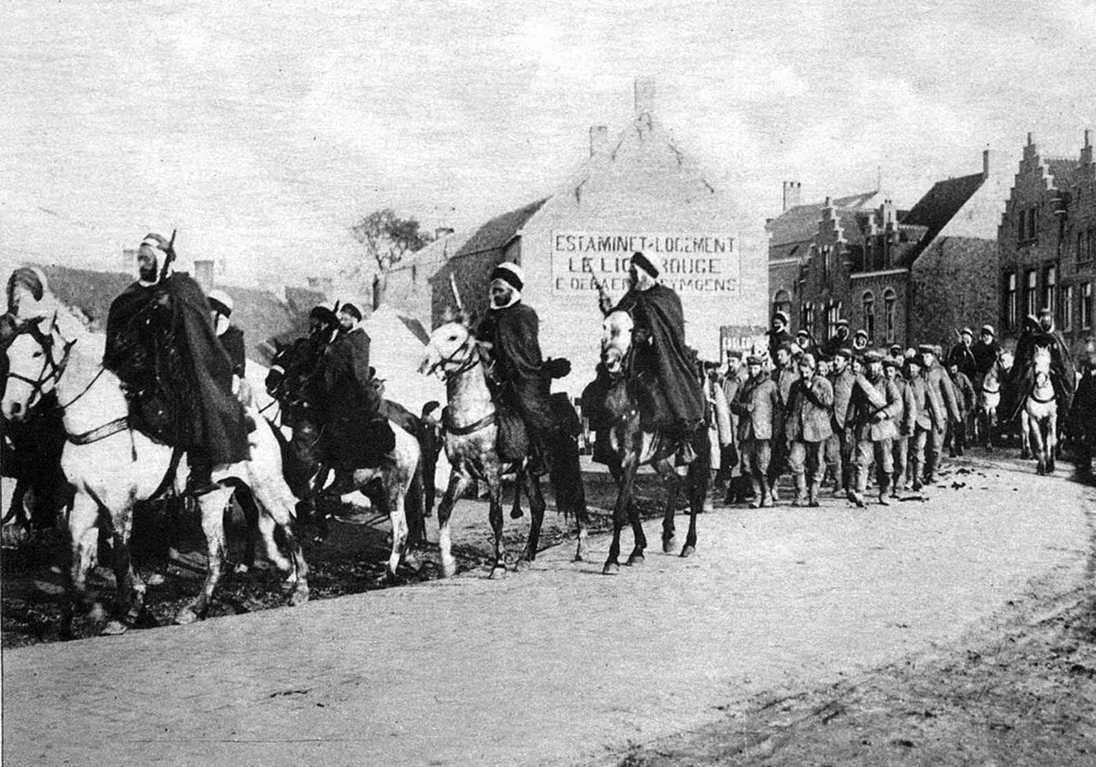 Algerian cavalry attached to the French Army, escorting a group of German prisoners taken in fighting in the west of Belgium.