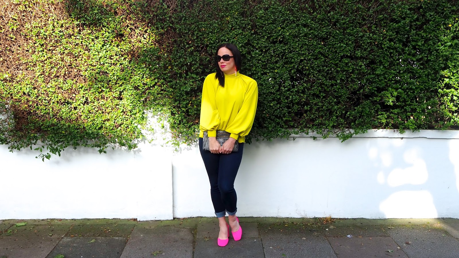 Neon yellow high neck balloon sleeve blouse, dark denim skinny jeans, neon pink square toe chunky heeled slingbacks and snake print clutch