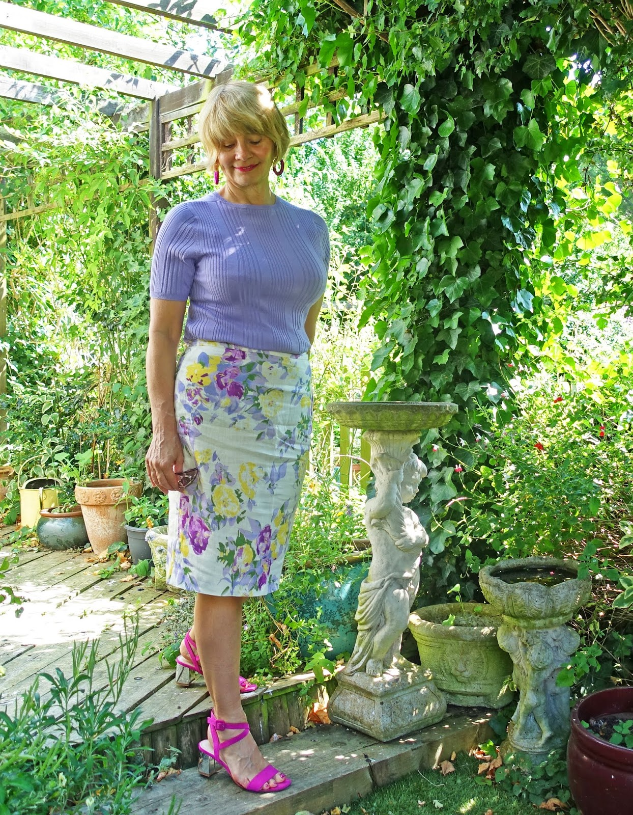 Mid life woman in lilac and yellow floral skirt and lilac top with pink sandals and earrings.