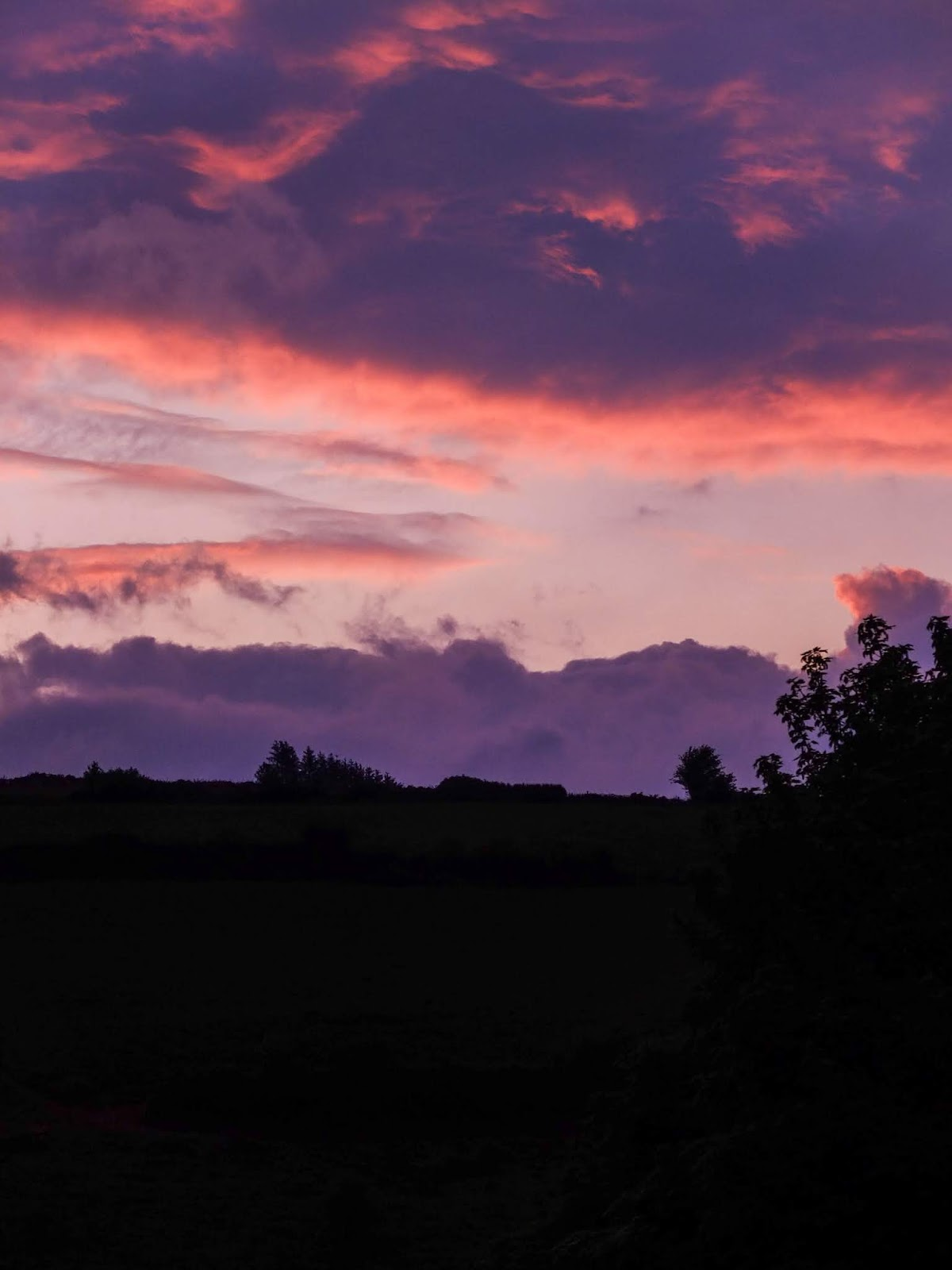 Pink and purple sunset clouds over a hillside in the Boggeragh Mountains in North Co.Cork, Ireland.