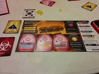 The yellow player's Evolution Slide. An image of a magnified bacterium on the top, with the 'core traits' (two listings of 'Infectivity +1' and one listing of 'Lethality +1') in the top left corner, five spaces to place Trait Cards (two of which, currently unoccupied, grant abilities so long as they remain unoccupied), three of which contain Trait Cards, and a Turn Summary listing along the right edge of the mat. The trait cards have a cost/point value in the upper left corner, next to which is the card's name (these three are Confusion, Mass Hysteria, and Blindness), and one or more abilities listed on the bottom (Confusion has 'Airborne' and 'Cold Resistance,' Mass Hysteria has 'Infectivity +1,' and Blindness has 'Lethality +1'). Some Event cards, unused Trait Cards, and a claimed Country Card, as well as some of the hexagonal yellow tokens, can be seen on the table nearby.