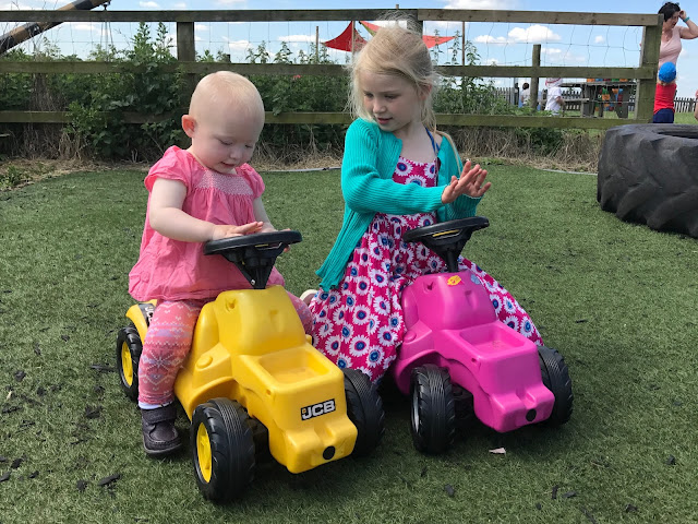 Sisters sitting on ride on colourful tractors at Lee Valley Farms