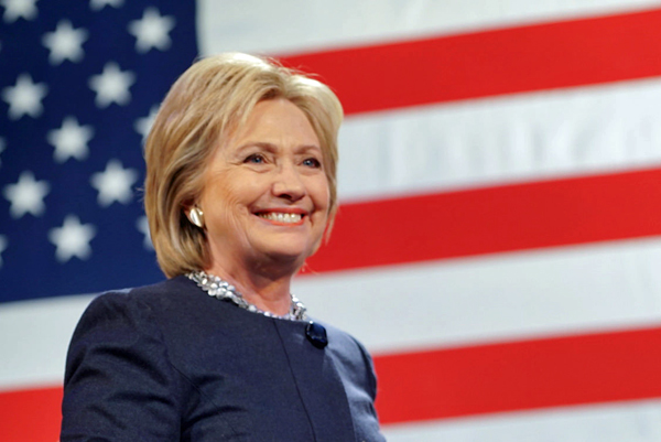image of Hillary Clinton standing in front of a U.S. flag and smiling