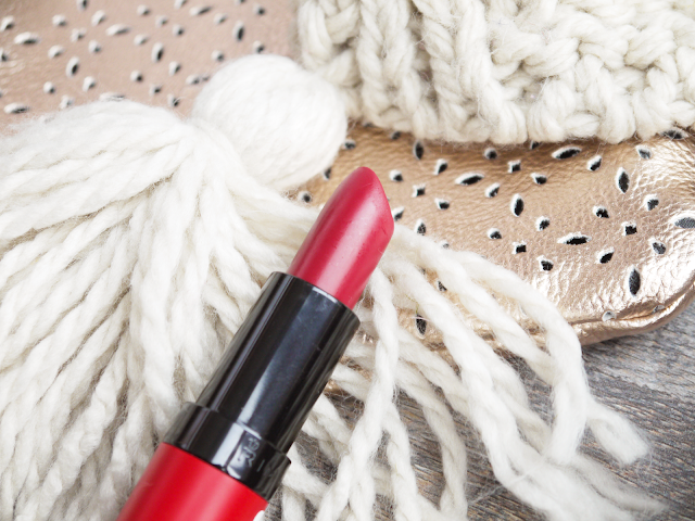 a berry red rimmel 107 lipstick lay across a cream knitted scarf and rose gold bag