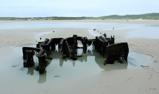 The shipwreck seems to be sinking into the sand