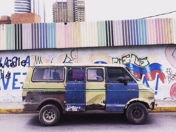 smashed up green and blue van next to a graffiti city wall