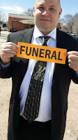 bald guy in black suit holding orange funeral sign classy undertaker mortuary home mortician tinder