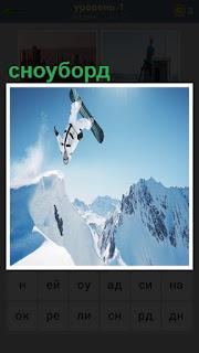 Парень высоко прыгает на сноуборде в зимнее время в горах