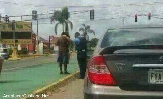 Policía orando por un mendigo en la calle