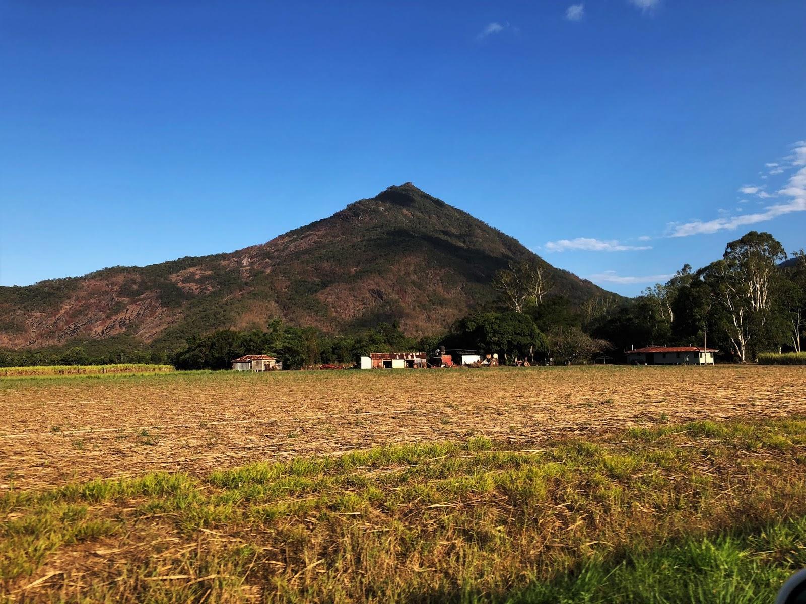 Góra o nazwie Walsh's Pyramid przypominająca piramidę na tle błękitnego nieba i suchego pola u jej podstaw.
