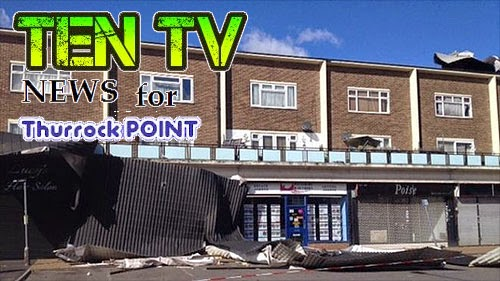 A line of shops with debris from flats roofing above being blown to the floor.