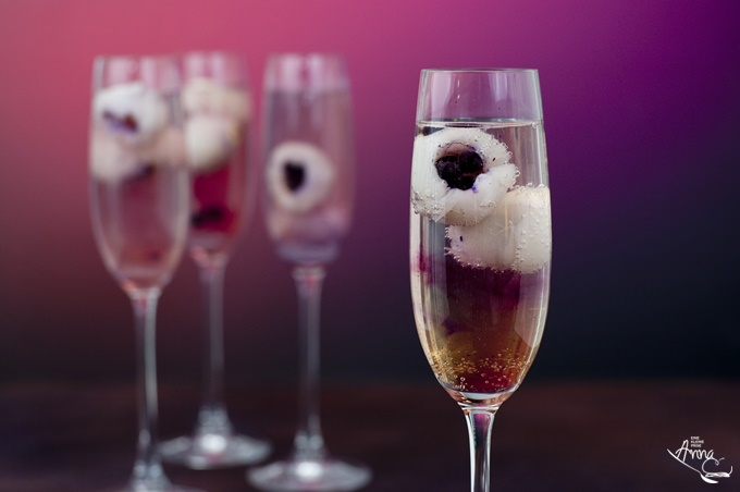 Prosecco mit Holunderblüten-Sirup und mit Blaubeeren gefüllte Litschi