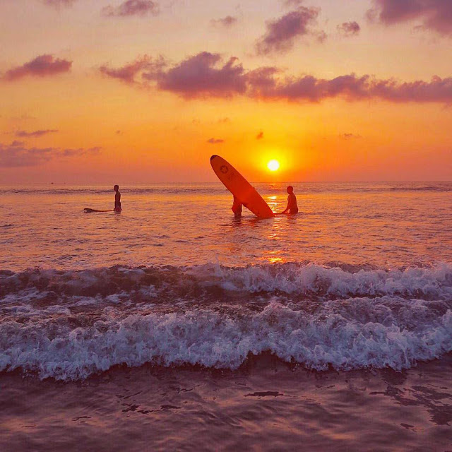 Surfing Dengan Latar Belakang Sunset di Pantai Kuta