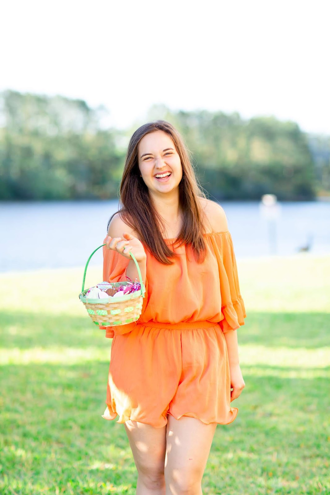 Brunette girl wearing orange off the shoulder chiffon Romper holding Easter basket with Tasty Treat Company Easter horse treats