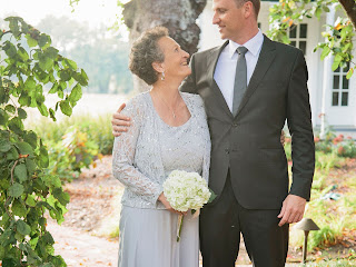 Mother and groom smiling embracing