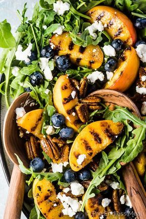 SAVE FOR LATER! Grilled Peach Salad is the ultimate summer side dish recipe. The peaches are grilled until smoky and extra sweet and served with arugula, blueberries, candied curry pecans, and a honey vinaigrette. Add some goat cheese or (paleo-friendly!) diced avocado and you've just made the best salad ever. | vegetarian + gluten-free + paleo option | #theendlessmeal #peaches #grilledpeaches #summer #bbq #grill #salad #arugula #pecans #vegetarian #sidedish #vinaigrette