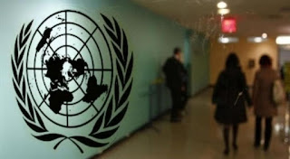 Photo of  UN logo with people walking by