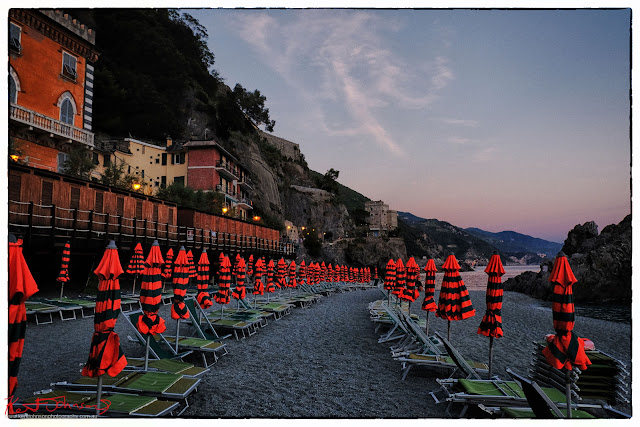 Umbrellas folded for the night, Monterosso al Mar, Cinque Terre,  Italy. Photo by Kent Johnson