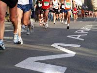 Maraton yazan bir asfalt yolda maraton koşusu yapan atletler