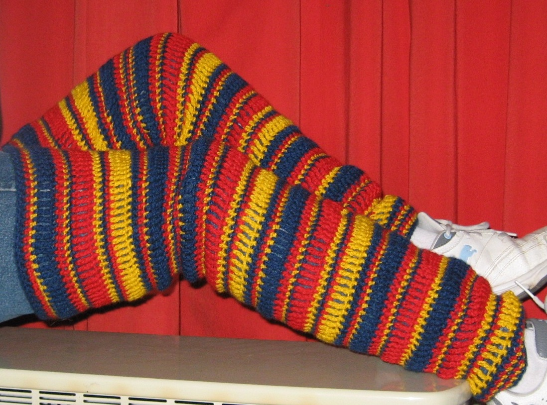 Legs covered from mid thigh to ankle with horizontally striped leg warmers. The stripes vary in width and colour, using navy, red and yellow.