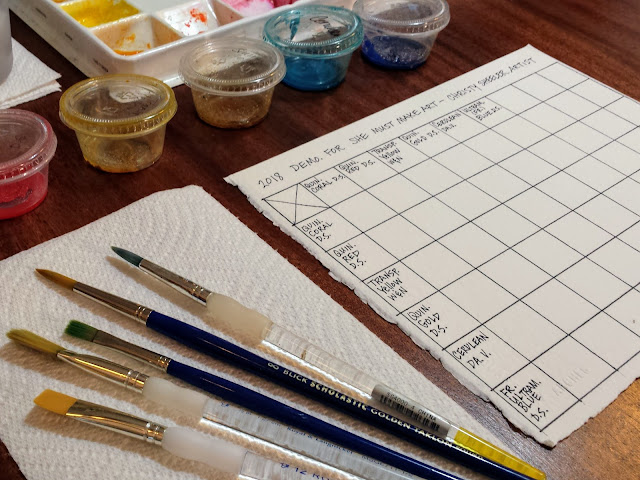 Workspace is arranged for mixing to begin. Brushes to left of watercolor paper.  Pigment in plastic cups arranged in order.
