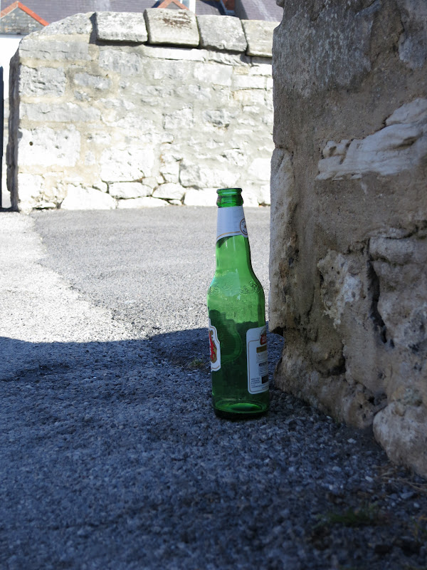 Green bottle abandoned by wall